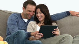 Couple using a computer tablet sitting on the sofa Footage