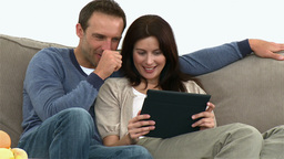 Couple using a computer tablet sitting on the sofa Stock Video Footage