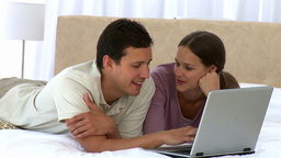 Cute happy couple looking at the laptop while lyin Stock Video Footage