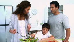 Woman cooking a salad with her son Stock Video Footage