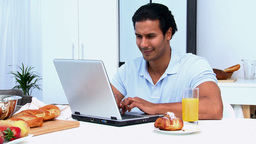 Happy man working on the laptop while having breakfast Footage