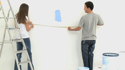 Couple measuring a wall during a renovation Footage