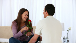 Man giving a rose to his wife sitting on the bed Stock Video Footage