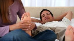 Lovely woman massaging her boyfriends feet Stock Video Footage
