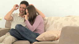 Couple laughing in front of the television Stock Video Footage