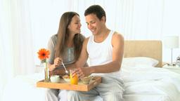 Beautiful couple having breakfast in the bedroom Footage