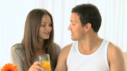 Woman kissing her boyfriend and drinking orange ju Footage
