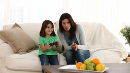 Little girl playing video games with her mother Footage