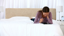 Smiling woman using a computer tablet lying on the Footage