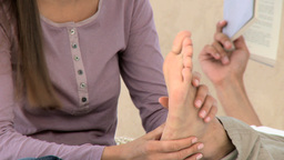 Beautiful woman massaging his boyfriends feet Footage