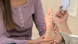 Beautiful woman massaging his boyfriends feet Footage