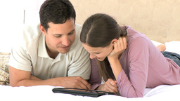 Smiling couple using a computer tablet while their are lying Footage