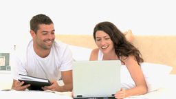 Happy couple using a laptop lying on the bed Footage