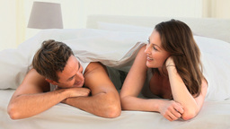 Pretty couple talking in their bed Stock Video Footage