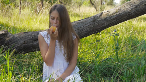 Girl eats a peach Stock Video Footage