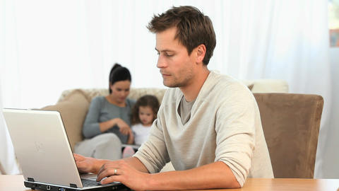 Man working on his laptop while his family is on t Stock Video Footage