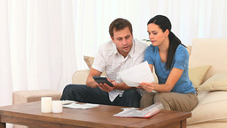 Worried couple calculating their domestic bills Stock Video Footage