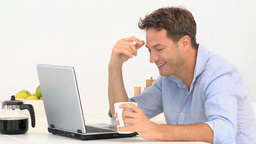 A man drinking while watching his laptop Footage