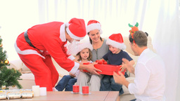 Santa Claus offering a gift to a little boy Footage