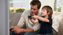 Little boy playing videogames with his father Footage