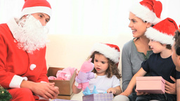 Santa Claus looking at children with their gifts Footage