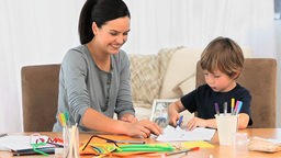 A mother smiling while her son is drawing Footage