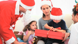 Santa Claus offering a gift to a little boy Stock Video Footage