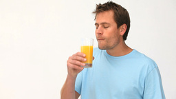 Cute man drinking a glass of orange juice Footage