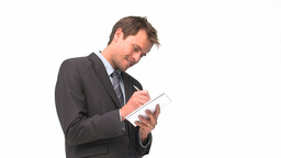 Smiling businessman writing on his notebook Stock Video Footage
