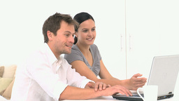 Lovely smiling couple searching something on their laptop Footage