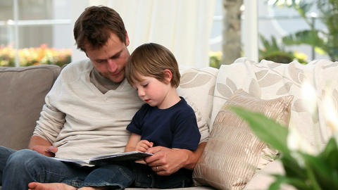 Man reading a book for his son Footage