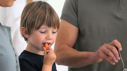 Boy eating vegetables while his father is serving Stock Video Footage