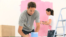 Couple painting a wall with the colour pink Stock Video Footage