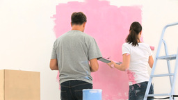 Couple painting a wall with the colour pink Footage