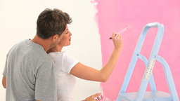 Lovely couple painting a wall in pink Footage