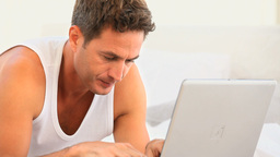 Worried man searching something on his laptop Stock Video Footage