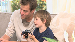 Boy playing video gemes with his father Footage