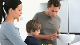 Man serving a salad to his family for lunch Footage
