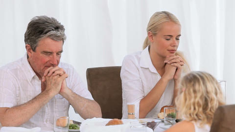 Family praying before dinner Stock Video Footage