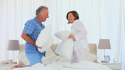 Retired couple playing on the bed with their pillows Stock Video Footage