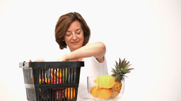 Senior woman putting fruit into a bowl Footage