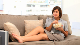 Casual brunette woman watching tv with popcorn Footage