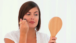 Brownhaired lady putting on make-up Stock Video Footage