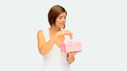 Cute brownhaired lady opening a gift Stock Video Footage