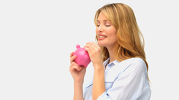 Cute blonde lady saving up her cash in a piggy ban Stock Video Footage