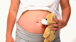 Pregnant woman holding a teddy bear Stock Video Footage