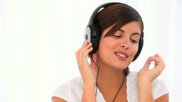 Brunette enjoying music Footage