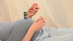 Pregnant lady playing with building blocks Footage