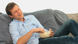 Man laughing in front of tv Stock Video Footage