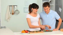 Woman teaching her boyfriend how to cook Stock Video Footage